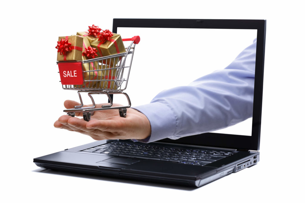 A man is holding a shopping cart in his hand through a laptop to depict holiday e-commerce sales.